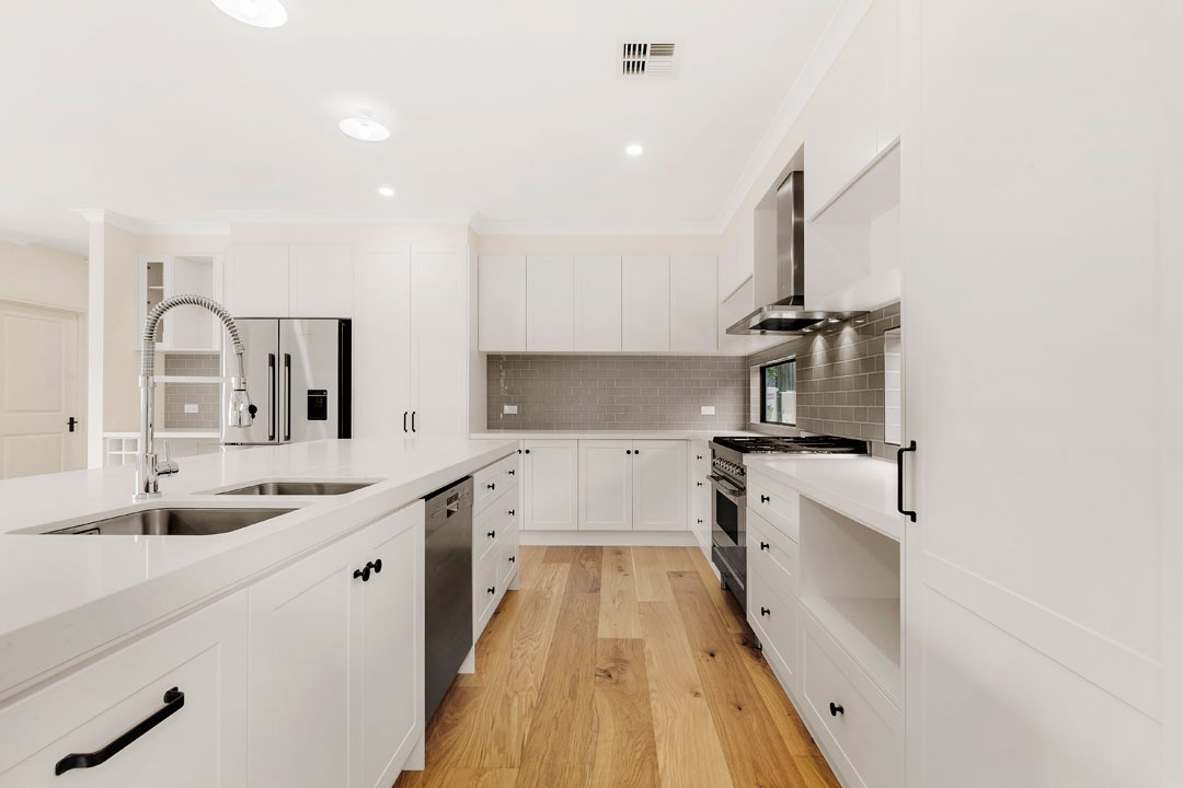 Busby Homes kitchen with timber floors and white cabinetry